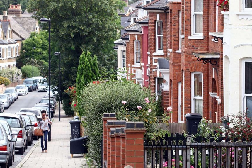 A pedestrian passes a row of terraced houses in southeast London.