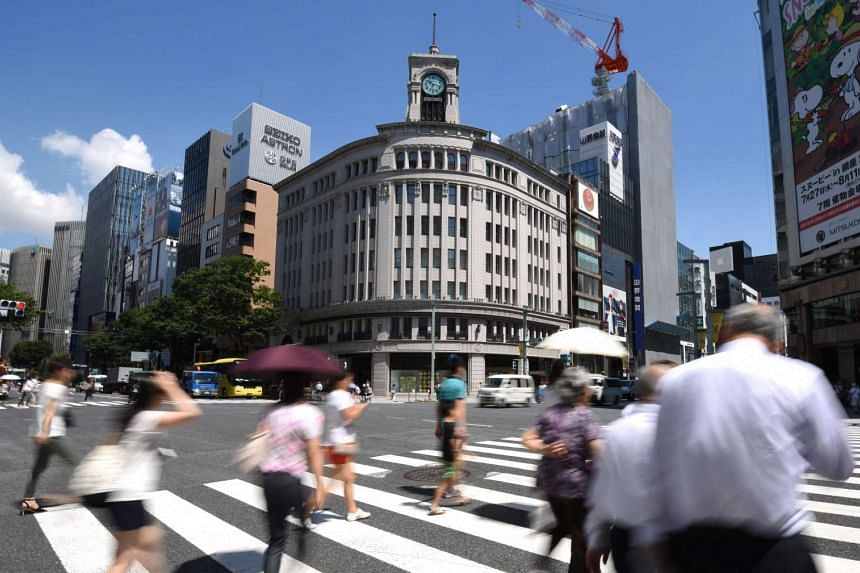 People walk on the street at the Ginza shopping district in Tokyo on July 29.
