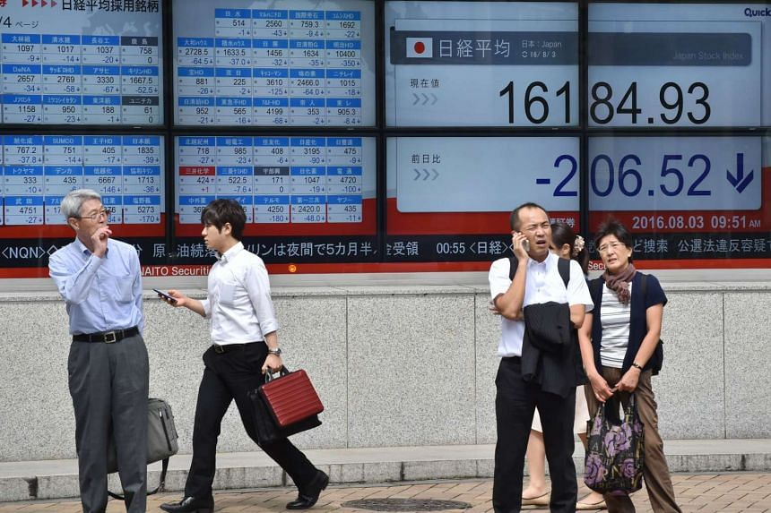Pedestrians stand in front of an electric quotation board displaying the Nikkei key index of the Tokyo Stock Exchange in Tokyo on Aug 3.
