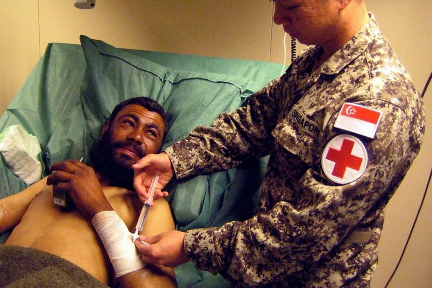 A member of the Singapore Armed Forces medical team administering treatment in Afghanistan in 2009.