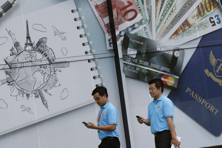 Pedestrians seen using their mobile phones as they walk past an advertisement in front of a bank in Bangkok, Thailand, August 11.