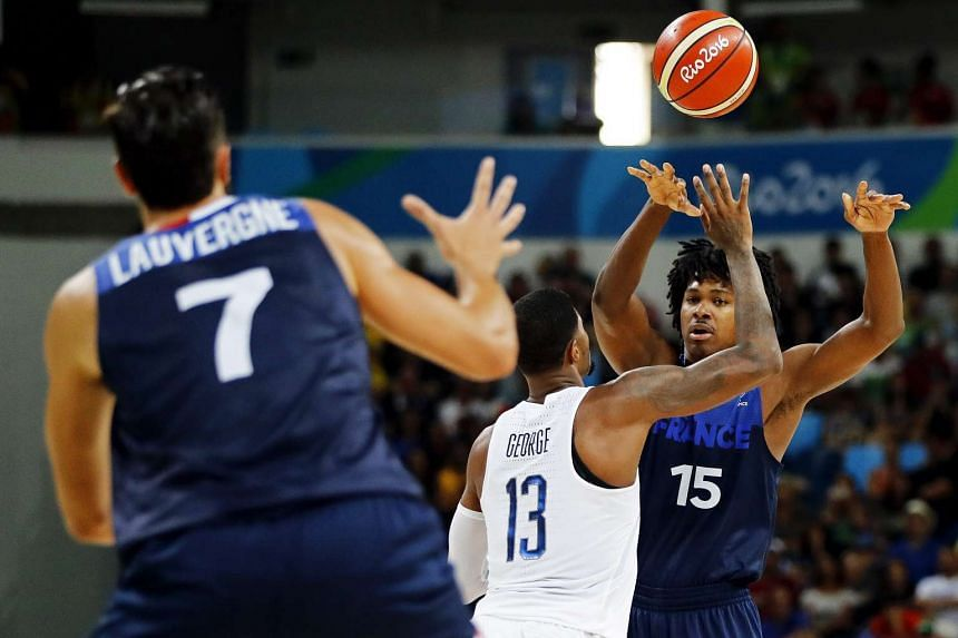 Paul George (centre) of the USA in action against Joffrey Lauvergne (left) and Mickael Gelabale (right) of France during the men's Basketball preliminary round game.