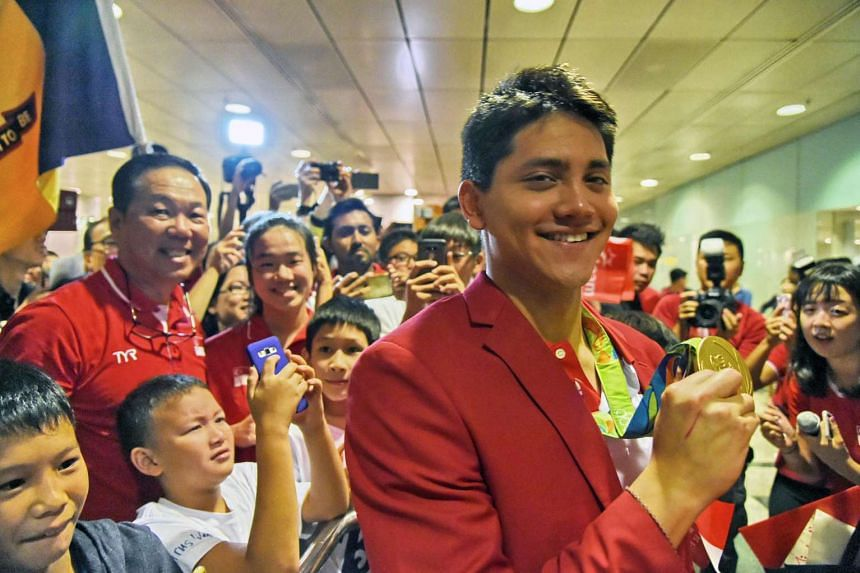 Singaporean swimmer Joseph Schooling holds his gold medal and poses upon arrival from Rio 2016 Olympic Games on Aug 15 at Changi International airport.