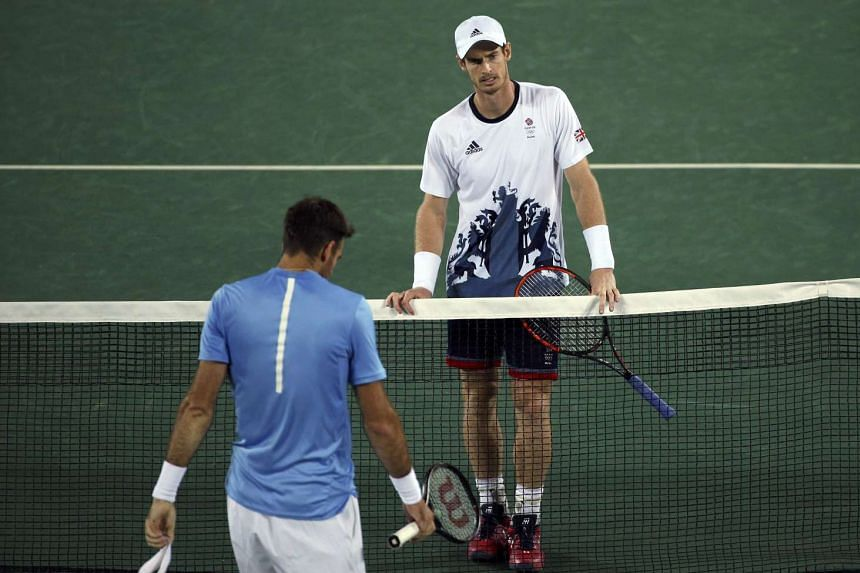 Andy Murray of Britain meets Juan Martin Del Potro of Argentina at the net after winning their match on Aug 14.