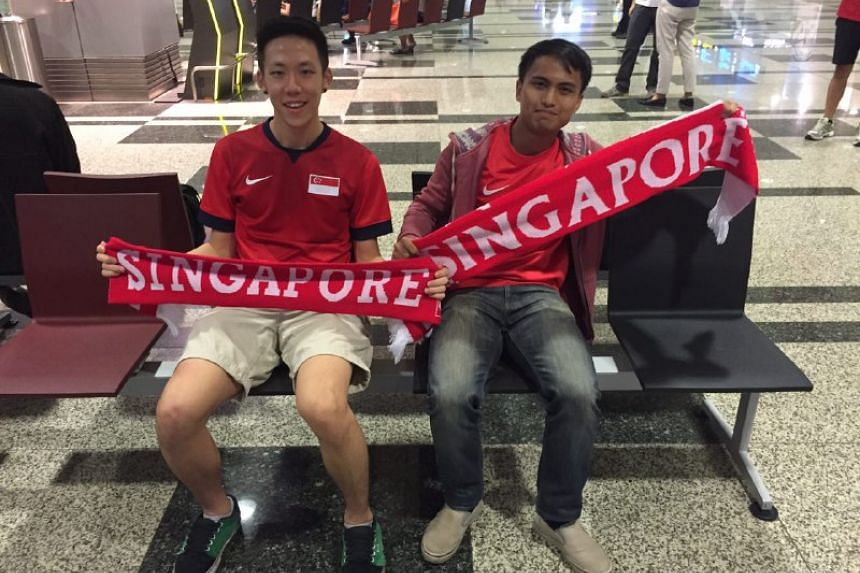 Student Phelan Wong (left) and Aziz Azhar, 25, who works part time in events logistics, at the airport to welcome Joseph Schooling.