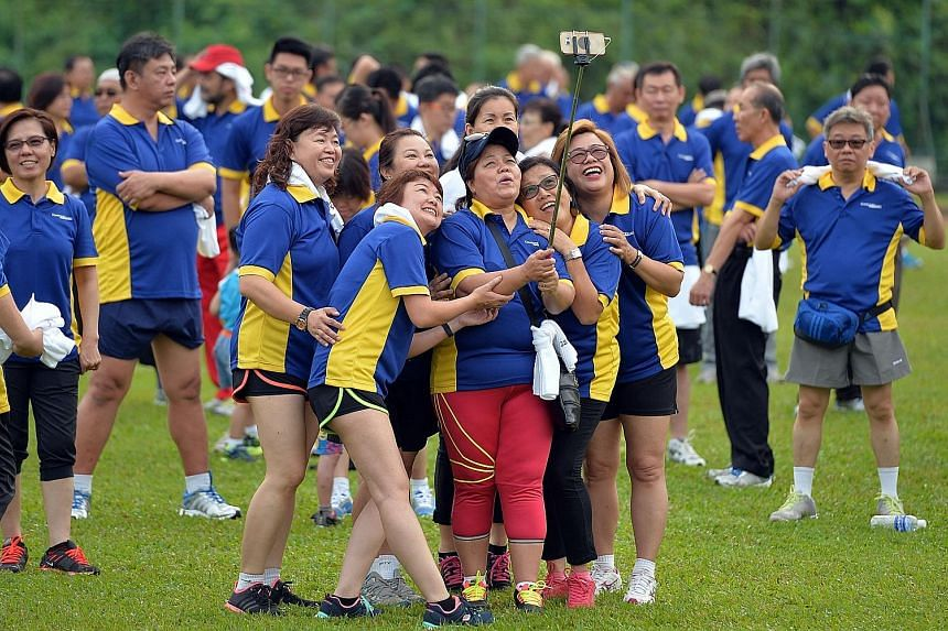 ConfortDelGro's women cabbies snapping a wefie before the morning workout yesterday. About 1,000 of the company's 37,000 taxi drivers got together with their families to exercise at Bukit Gombak Stadium.