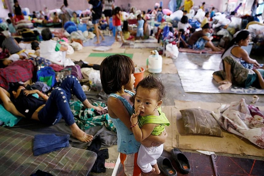 Residents waiting to be evacuated on Saturday after their homes were swamped by floods brought by monsoon rain in San Mateo municipality, Rizal province, east of Manila. More than 70,000 people have had their houses swamped by floodwaters, according