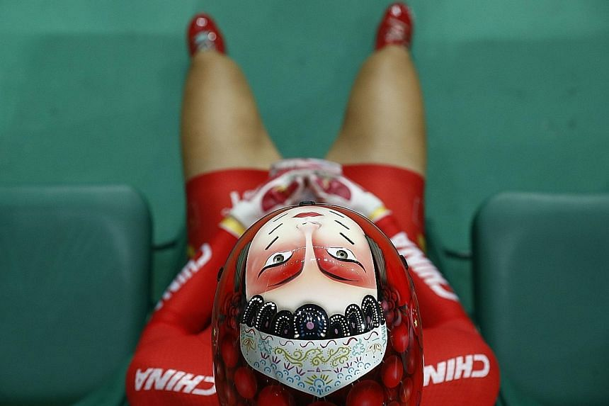 Winning shot: A face is painted onto the helmet of China's Zhong Tianshi, as she waits to compete in the women's keirin track cycling second round at the Velodrome on Saturday. She went on to finish 11th in the event won by the Netherlands' Elis Ligtlee.