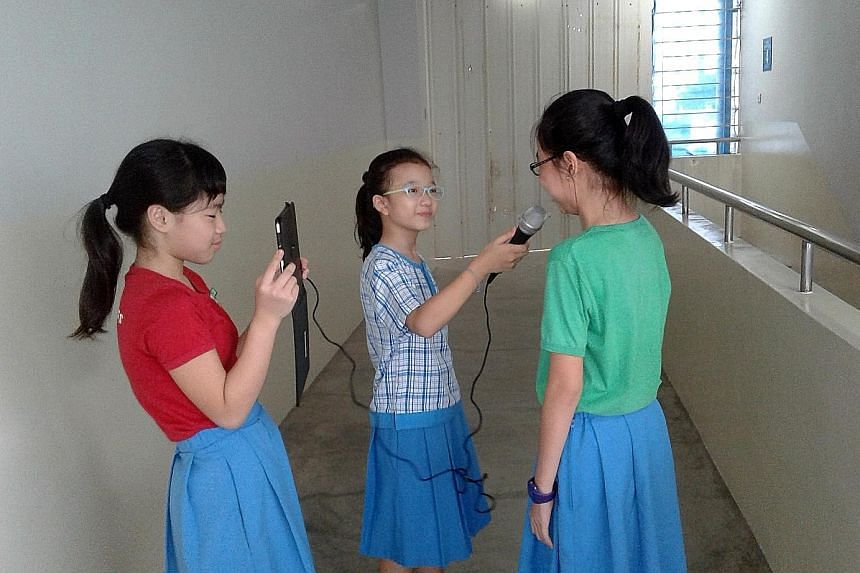 Two Jiemin Primary pupils, armed with a microphone and an iPad, interviewing a schoolmate.