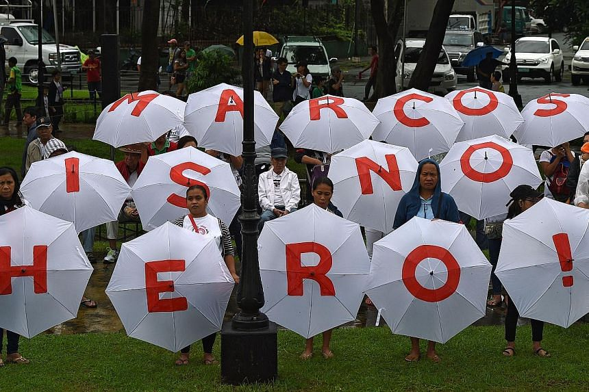 Protesters holding umbrellas with an anti-Marcos slogan in a Manila park yesterday. Thousands gathered in protest at plans to honour late dictator Ferdinand Marcos with a state burial.