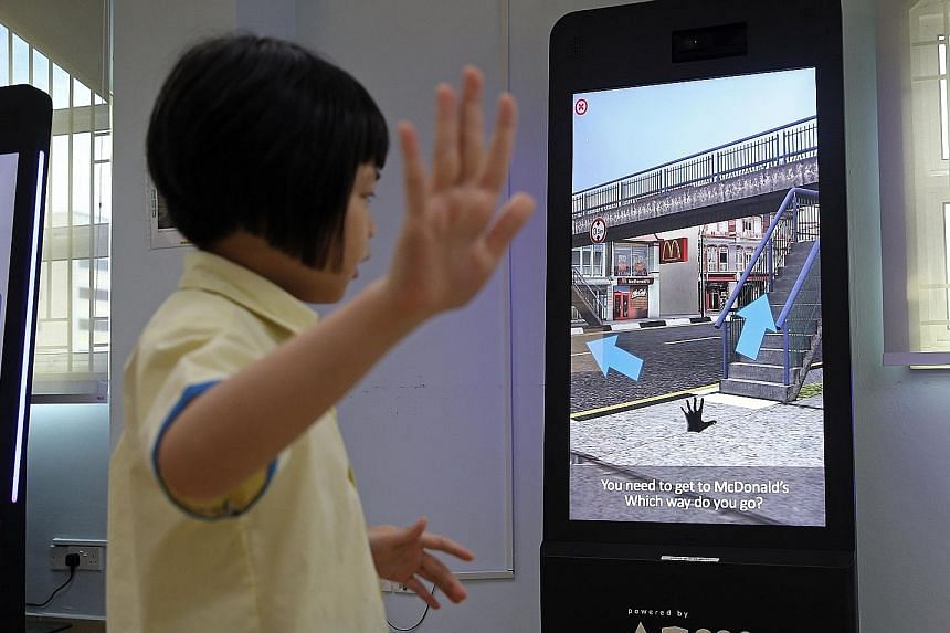 Pupil Stefanie Ang, eight, learning how to use the overhead bridge through a virtual reality game.