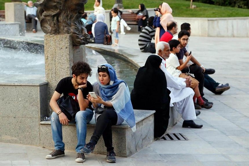 Young Iranians play Pokemon Go on their smartphones at the Mellat Park, northern Teheran, Iran, on Aug 12.