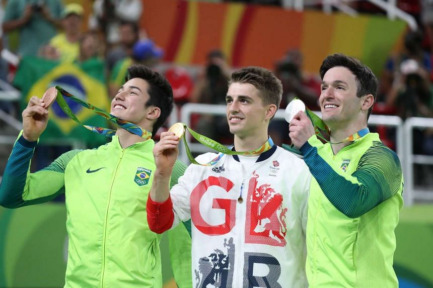 Bronze medalist Arthur Mariano of Brazil (left to right), gold medalist Max Whitlock of Great Britain, and silver medalist Diego Hypolito of Brazil smile during the medal ceremony.