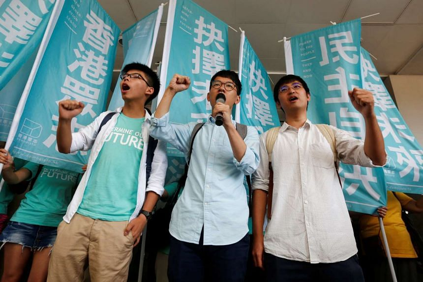 Student leaders (from left) Joshua Wong, Nathan Law and Alex Chow chant slogans before a verdict, on charges of inciting and participating in an illegal assembly in 2014.