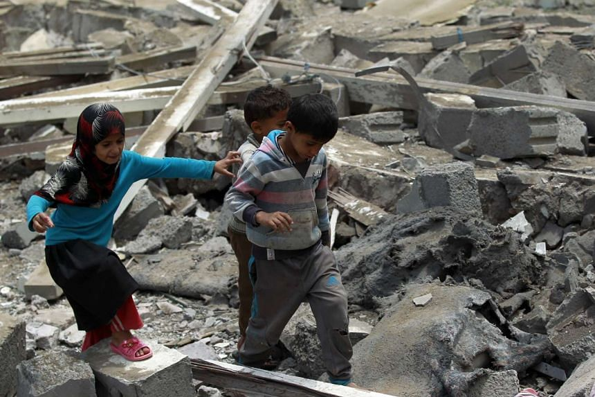Yemeni children walk amidst the rubble of a house in Yemen's Huthi rebel-held capital Sanaa, after it was reportedly hit by a Saudi-led coalition air strike.