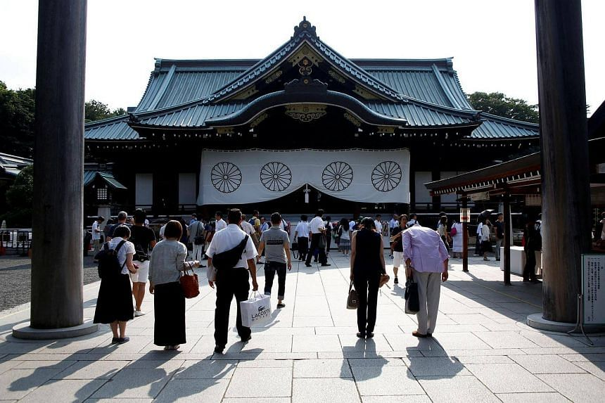 Visitors bow their heads towards the Yasukuni Shrine, on August 14.
