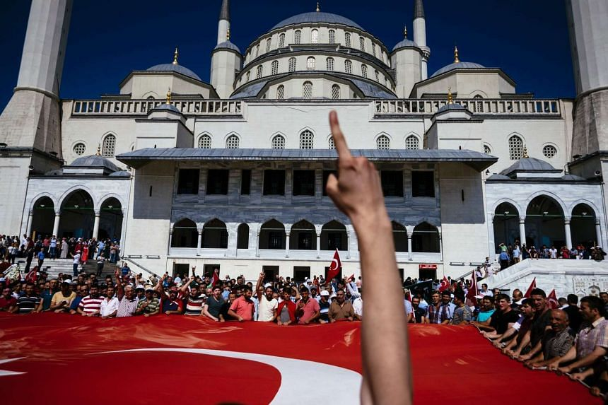 Pro-Erdogan supporters holding a giant Turkish flag during funerals of the victims of the coup attempt at Kocatepe Mosque in Ankara on July 17, 2016.