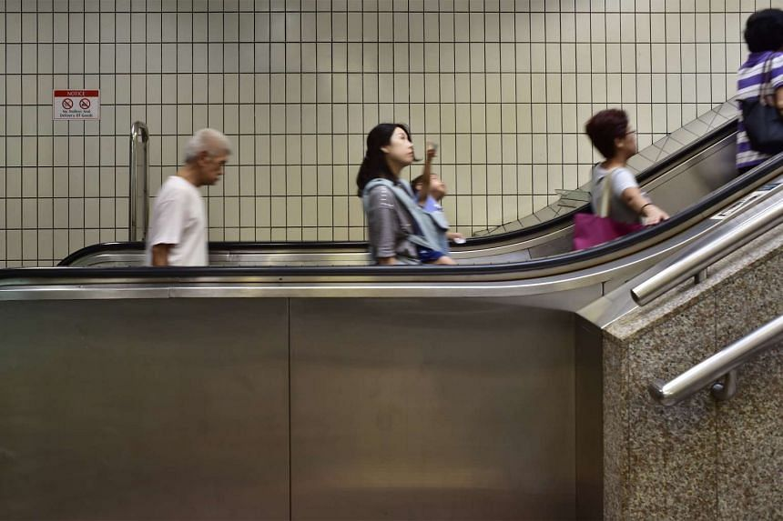 Commuters taking the escalator up at the Toa Payoh MRT station towards the Toa Payoh Bus Interchange.