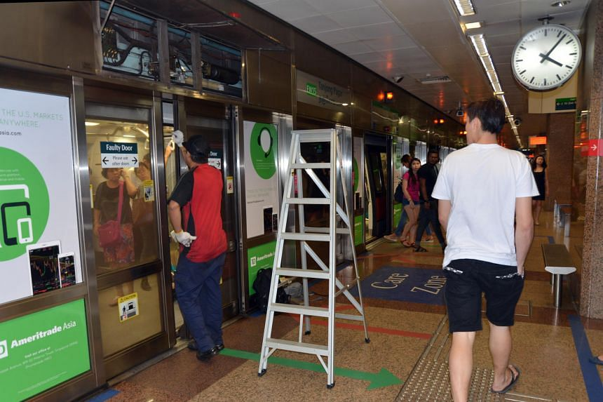 MRT staff repairing the faulty door where the smoke is seen coming out from.