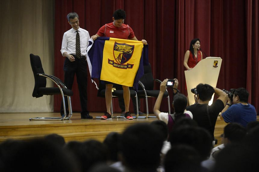 Joseph Schooling poses with the ACS flag after receiving it from the president of the ACS Old Boys' Association Lim Tat.