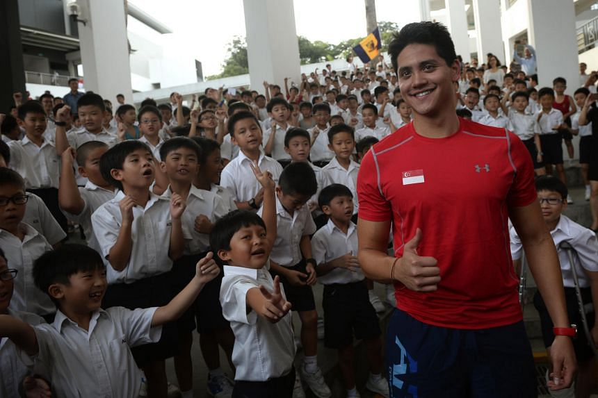 Joseph Schooling poses with ACS (Junior) Primary 1 and 2 students during his visit to his alma mater on Aug 16.