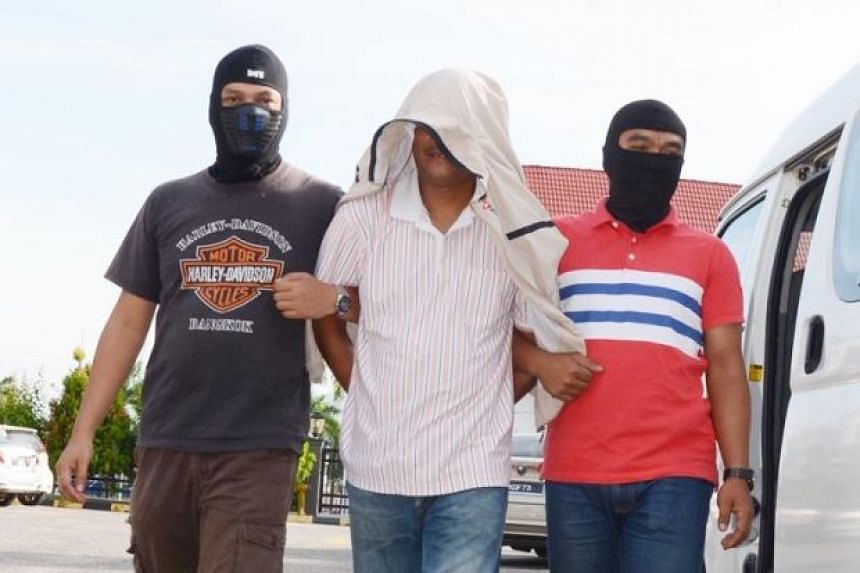 Saidin Yaacob (centre), who has been accused of recruiting two individuals into ISIS, is led away by masked policemen.