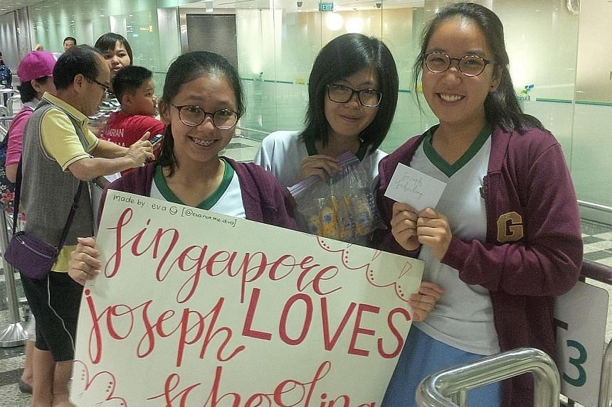Singapore Chinese Girls' School students (from left) Eva Wee, Meagan Goh and Naomi Low bearing gifts they made for Schooling. Many fans were there with homemade gifts and banners thanking their idol. Changi Airport welcoming the aircraft Schooling wa
