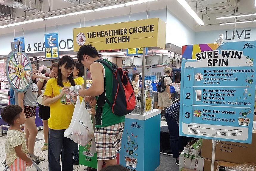 Shoppers at one of the HPB touchpoints at FairPrice Xtra in Ang Mo Kio Hub. Those who buy three Healthier Choice Symbol products can spin the wheel to win a prize.