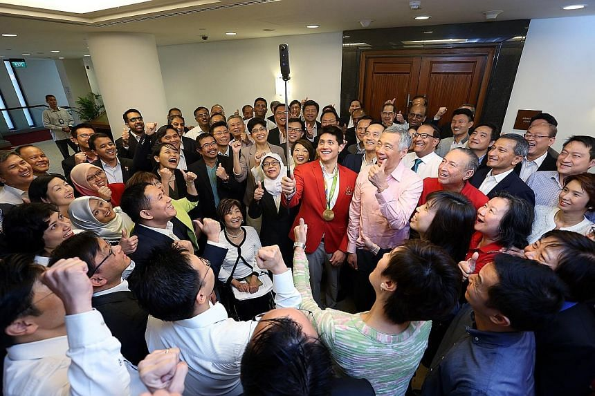 """Schooling snapping a photo with PM Lee and other MPs yesterday. In a Facebook post, the Prime Minister said the 21-year-old has """"shown a new generation of aspiring athletes that dreams are worth striving for"""". The House gave Schooling a 30-second sta"""