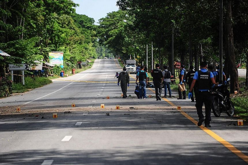 Members of a bomb squad unit inspecting the scene of a blast in the Bacho district of Thailand's southern Narathiwat province yesterday.