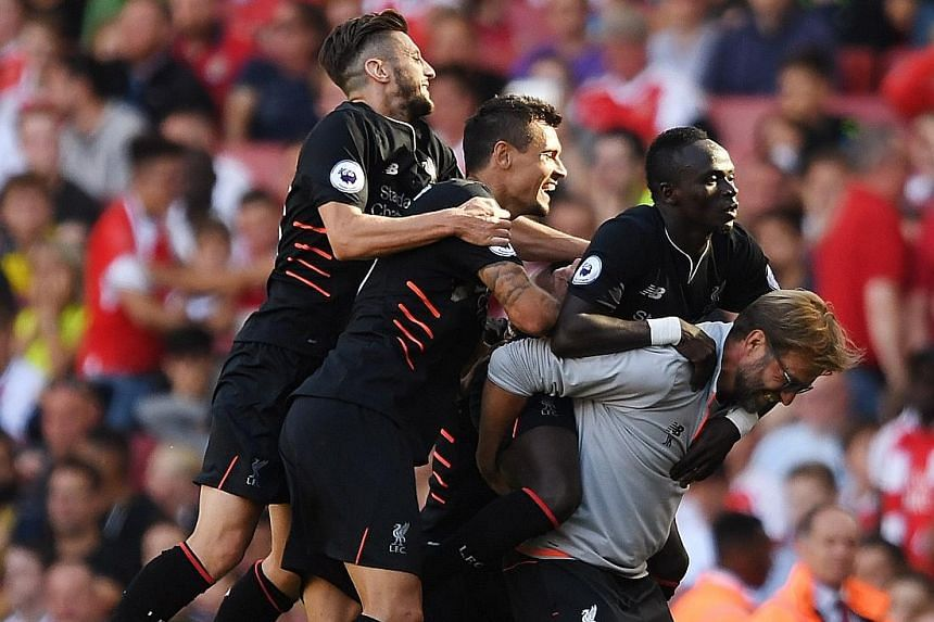 An exuberant Jurgen Klopp carrying Sadio Mane after the forward's fourth goal in their 4-3 win over Arsenal, with Adam Lallana (left) and Dejan Lovren joining in the celebrations.