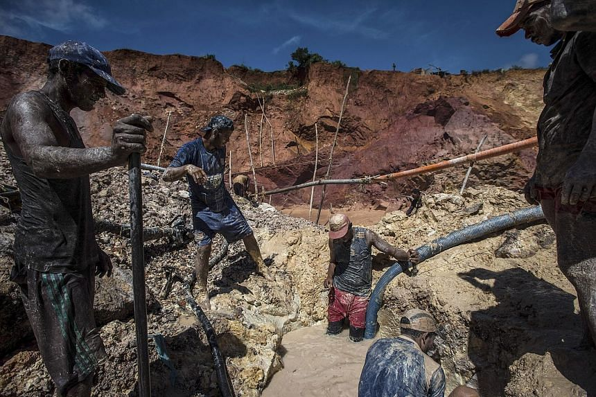 Workers at an illegal gold mine outside Las Claritas, Venezuela. At least 70,000 people have flocked to mines, both legal and illegal, over the past year. As they hunt for gold in the watery pits where mosquitoes breed, they are catching malaria in t