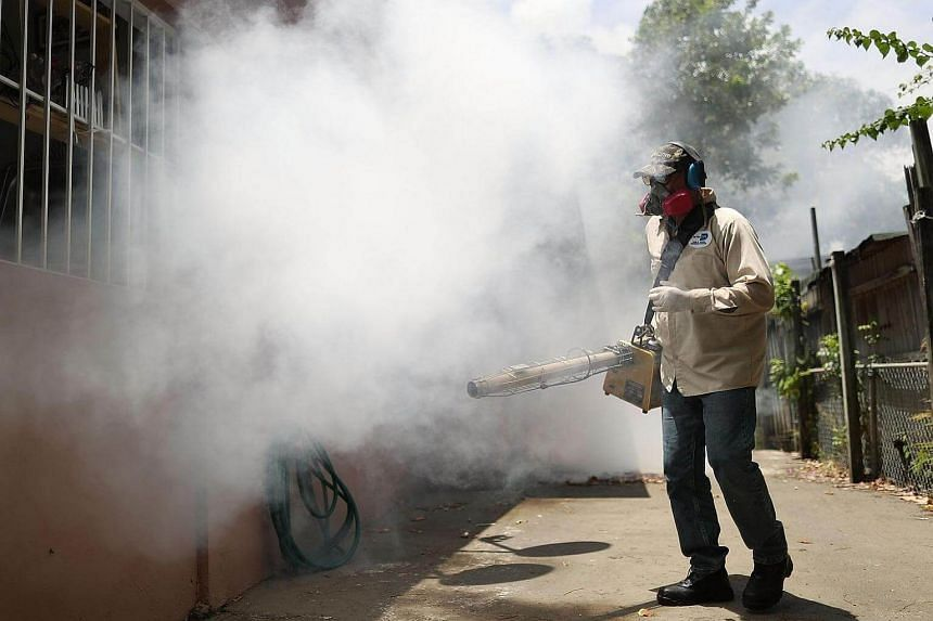 A man seen spraying  pesticide to kill mosquitos in the Wynwood neighbourhood as the county fights to control the Zika virus outbreak on August 2 in Miami, Florida.