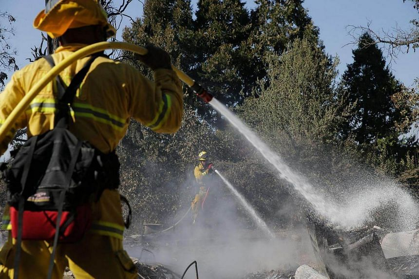 Firefighters work to put out lingering hot spots left by the Clayton Fire on August 15.