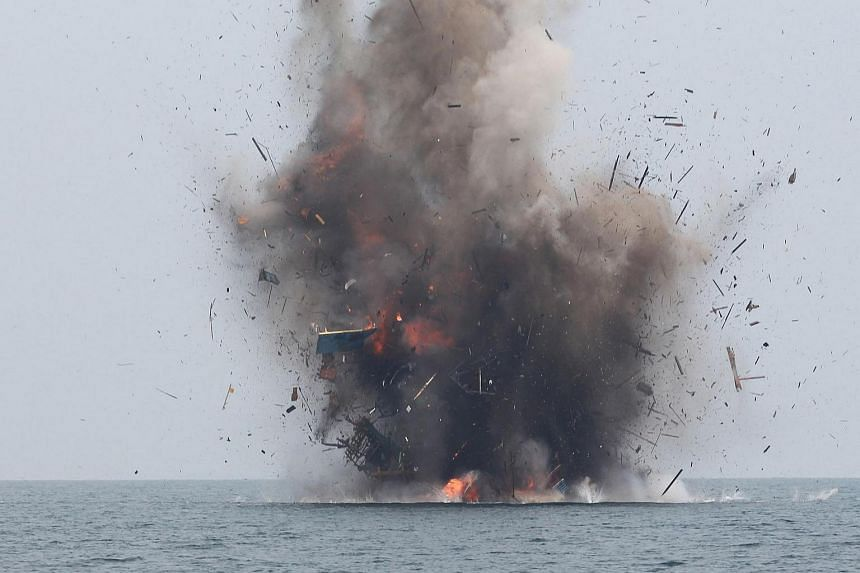This file photo taken on April 5 shows an illegal fishing boat being blown up with explosives by Indonesian authorities in Kuala Langsa, Aceh province.