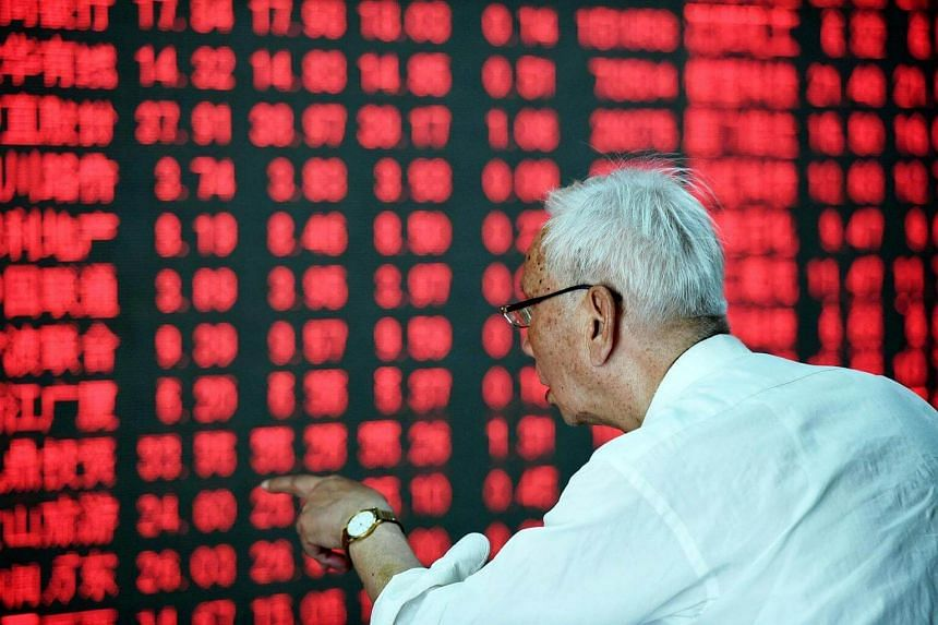 A Chinese investor gestures in front of a screen showing stock market movements at a securities firm in Hangzhou, eastern China's Zhejiang province on May 31.