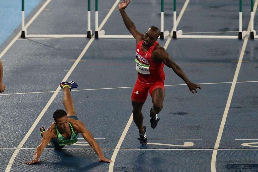 Joao Vitor de Oliveira of Brazil (left) falls next to Mikel Thomas of Trinidad and Tobago during the men's 110m Hurdles heats.