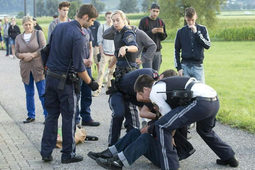 Austrian policemen arrest a suspect on Aug 16, 2016 at the train station Sulz-Röthis in Vorarlberg, Austria, after he had attacked two train passengers with a knife.