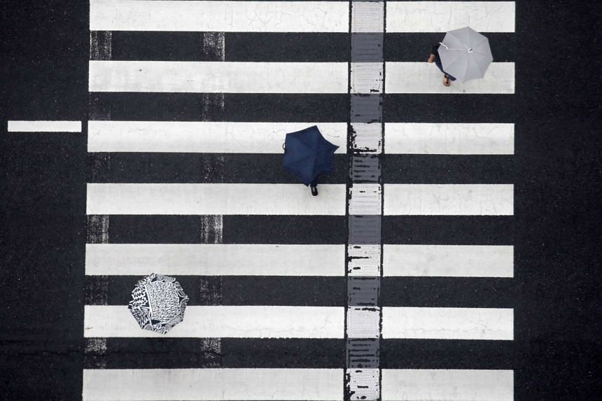 Pedestrians use umbrellas as they cross the street at a crosswalk in the rain in Tokyo on Aug 16, 2016.