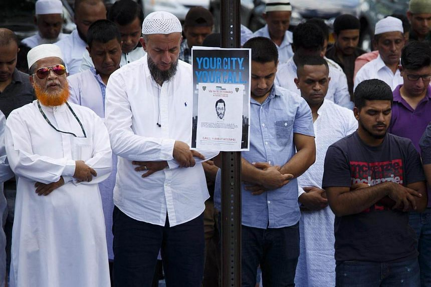 Community members pray outside the Al-Furqan Jame Masjid mosque before a funeral prayer for Imam Maulana Alauddin Akonjee and Thara Miah, in Queens, New York, on August 15.