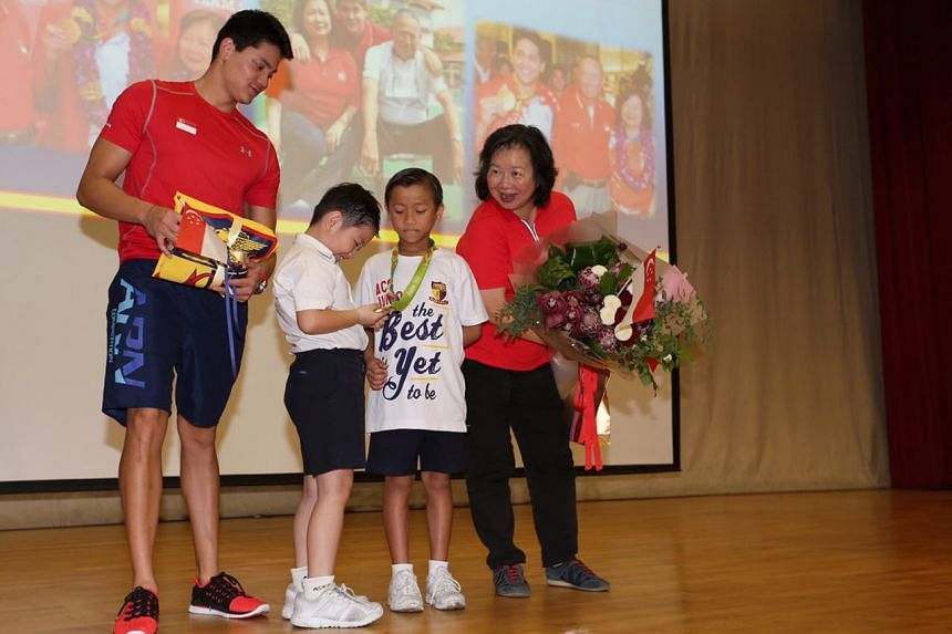 Darion Pang Jun Jia admiring Schooling's gold medal after receiving it from Schooling and hands it over to Marcus Lim while Schooling's mother May looks on.