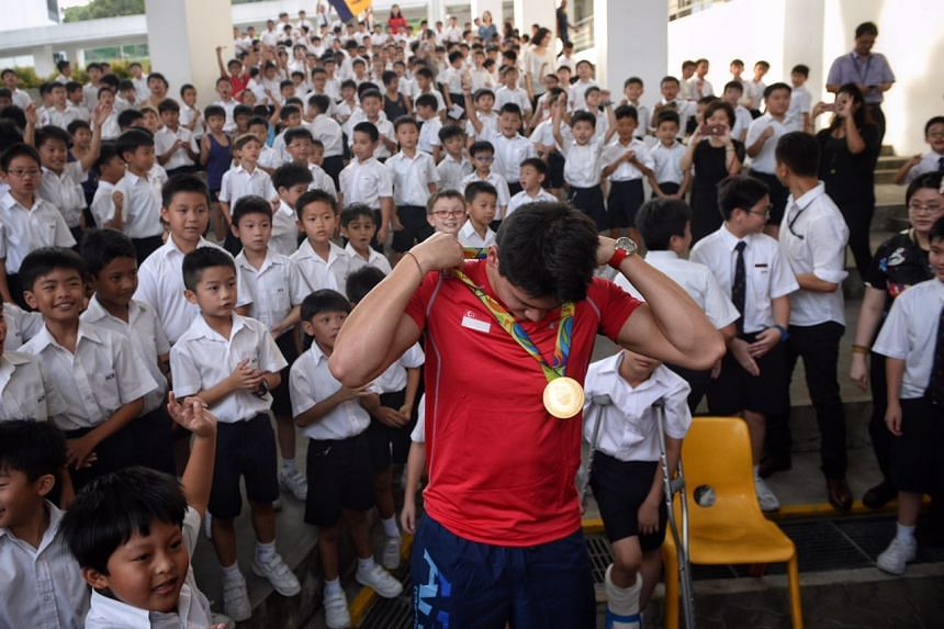 Joseph Schooling puts on his Olympic gold medal as students look on.