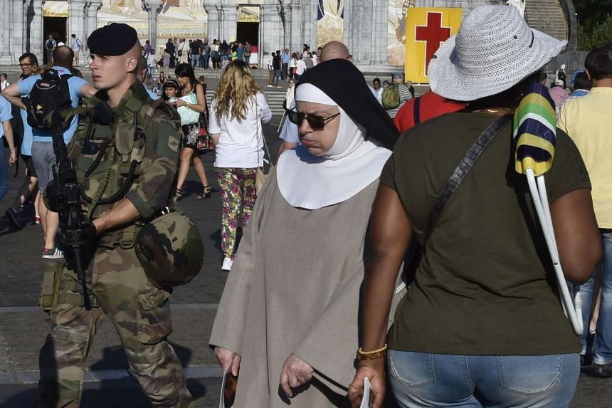 A nun walks past a French soldier patroling inside the sanctuary of Notre Dame de Lourdes during the annual Catholic pilgrimage of Lourdes on Monday (Aug 15).
