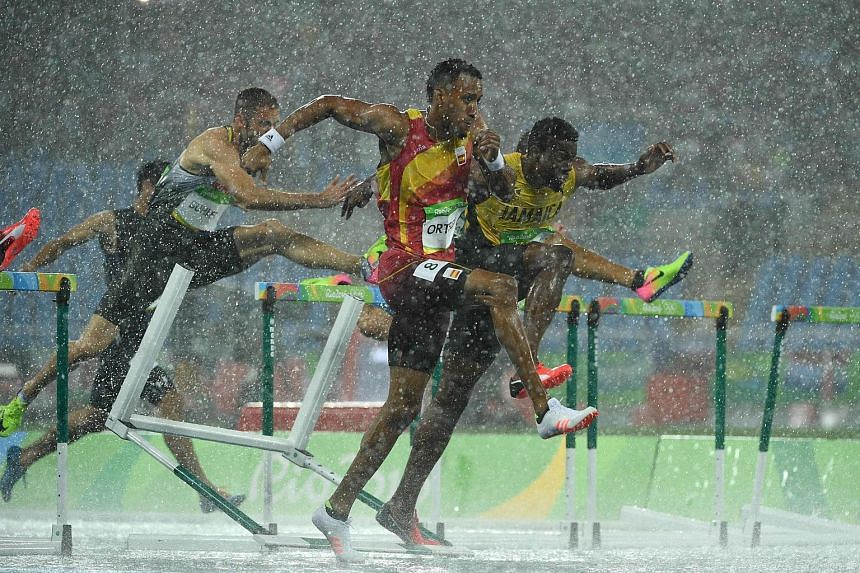 Spains' Orlando Ortega (centre) and Jamaica's Deuce Carter (right) compete in the rain-soaked Men's 110m Hurdles Round 1at the Rio 2016 Olympic Games in Rio de Janeiro on August 15.