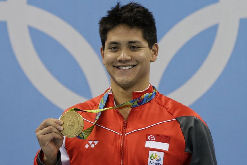 Singaporean swimmer Joseph Schooling poses with his gold medal at the medal ceremony in Rio.
