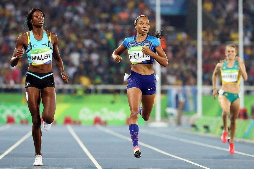 Shaunae Miller (left) of Bahamas and Allyson Felix (centre) of the US compete during the women's 400m semi finals of the Rio 2016 Olympic Games Athletics, Track and Field event, August 14.