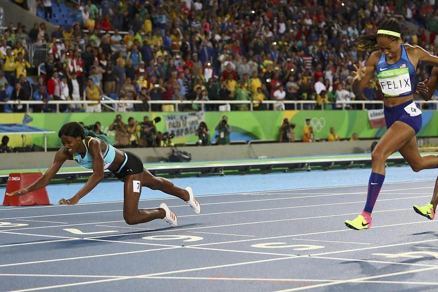 Shaunae Miller of Bahamas throws herself across the finish line to win the gold medal ahead of Allyson Felix of US (right) and Shericka Jackson of Jamaica (not pictured).