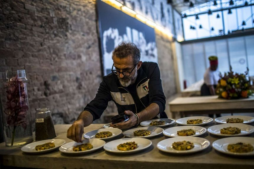 Italian chef Massimo Bottura sprinkling spices onto Mediterranean-style couscous before it is served to guests at Refettorio Gastromotiva, a feeding centre in Rio de Janeiro.