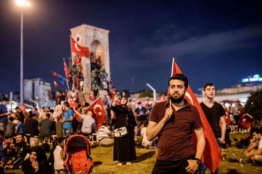 A Pro-Erdogan supporter holds a Turkish national flag during a rally at Taksim square in Istanbul on July 18, 2016 following the military failed coup attempt of July 15. Turkey has been carrying out raids against suspected plotters, raising concerns