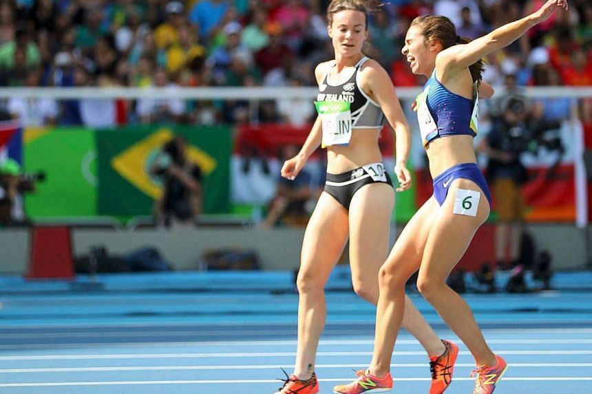 Nikki Hamblin of New Zealand stops running during the race to help fellow competitor US' Abbey D'Agostino after the latter suffered a cramp.